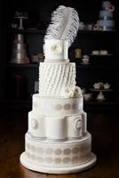 Five tier cake with ruffles antique cameos and silver accented ranunculus flowers