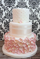 Pink wedding cake covered with pink sugar flowers and satin ribbon.