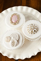 Fondant covered cupcakes with vintage brooches and pearls.