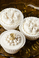 Fondant covered cupcakes with small gumpaste roses and pearls.